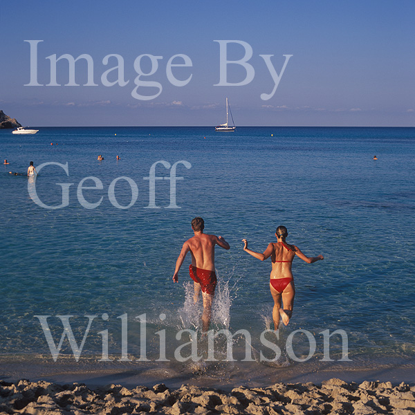 GW30310-60 = Scene at Cala Agulla - young couple running into the sea